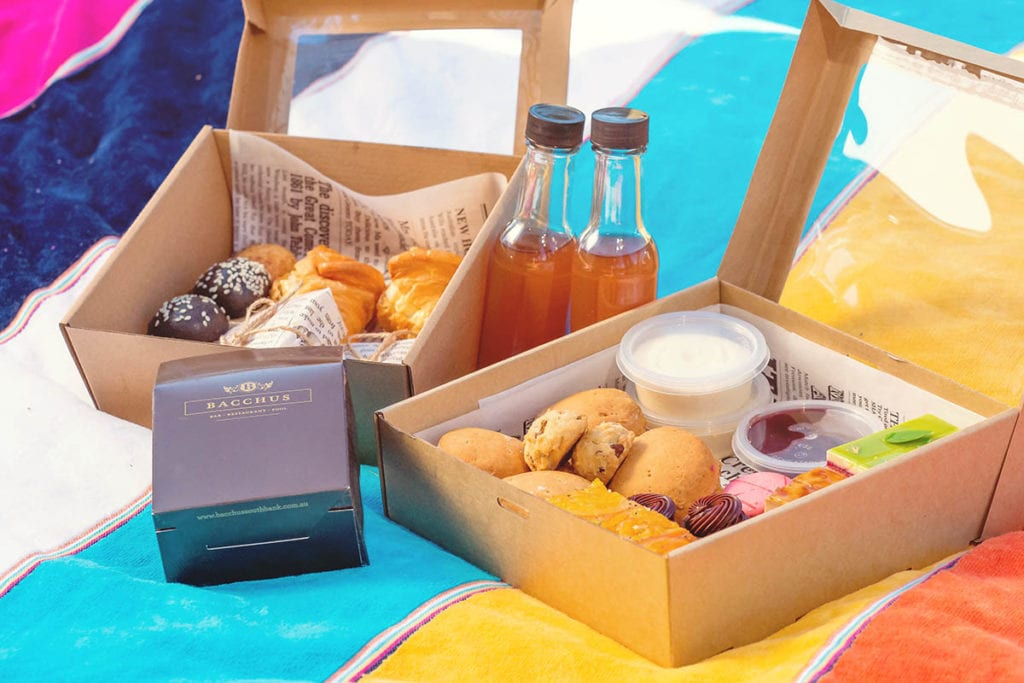 Colourful picnic blanket with food and drinks