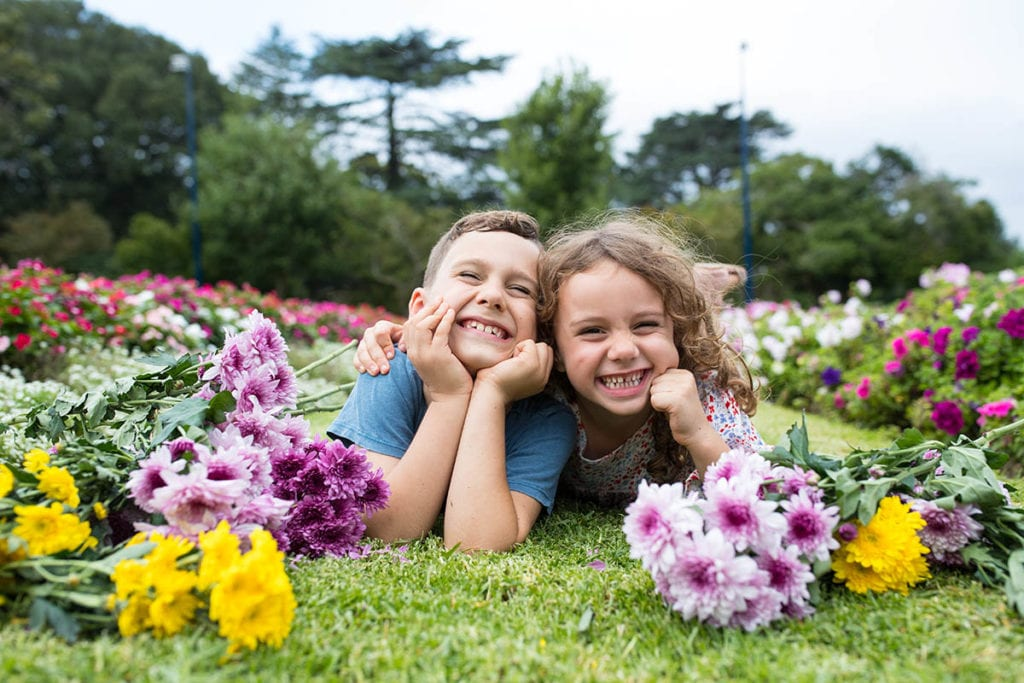 two chidren play with flowers