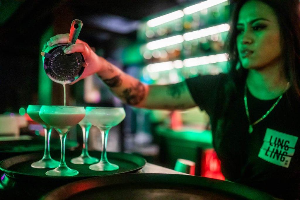 barwoman pours cocktail