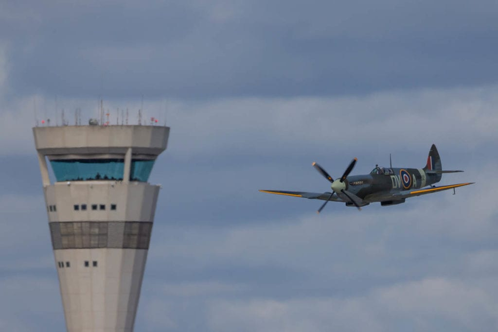 Old plane flys by airport tower