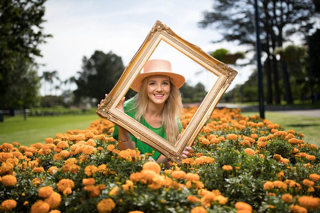 Woman with picture frame in park