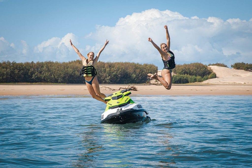 women jump from jet ski